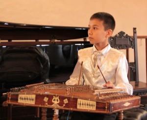 """Il vincitore Rossini International 2016: il giovane Izzatilla che suona il Chang, uno strumento popolare dell'Uzbekistan. Con le bacchette, toccherà le corde del """"cimbalo"""" per suonare Il Barbiere di Siviglia."""