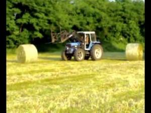 Un trattore che carica balle di fieno (foto tratta dal web)