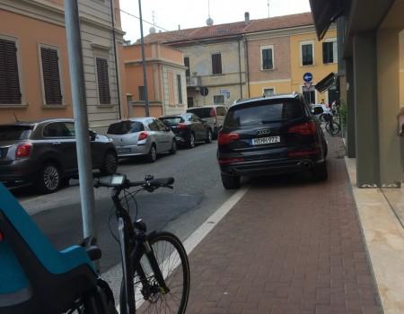 Un'auto tedesca parcheggiata sul marciapiede in Via Montello, in centro