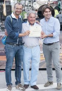 Bruscoli (al centro) premiato un anno fa da Ricci e Biancani